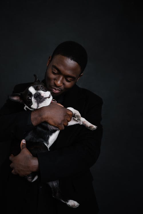 African American man holding dog