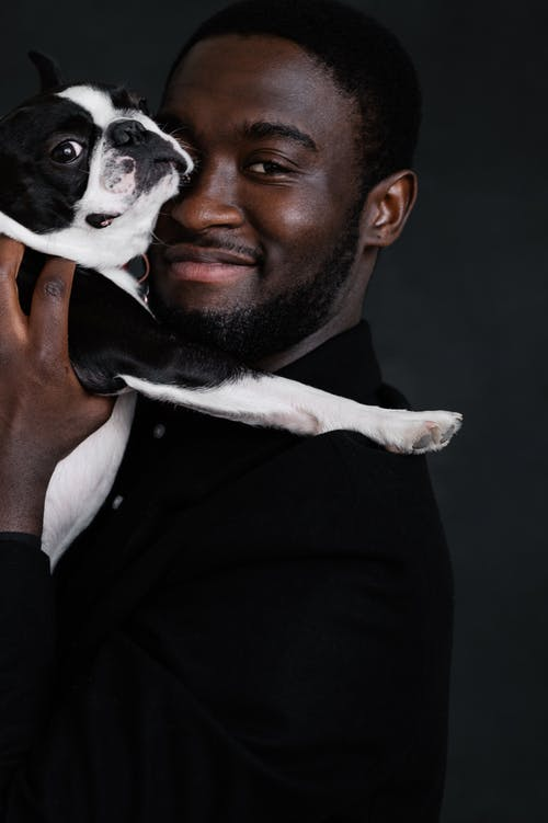 Black owner with adorable Boston Terrier