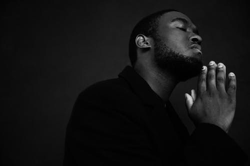 Monochrome handsome unshaven African American male in black suit praying with hands clasped under chin