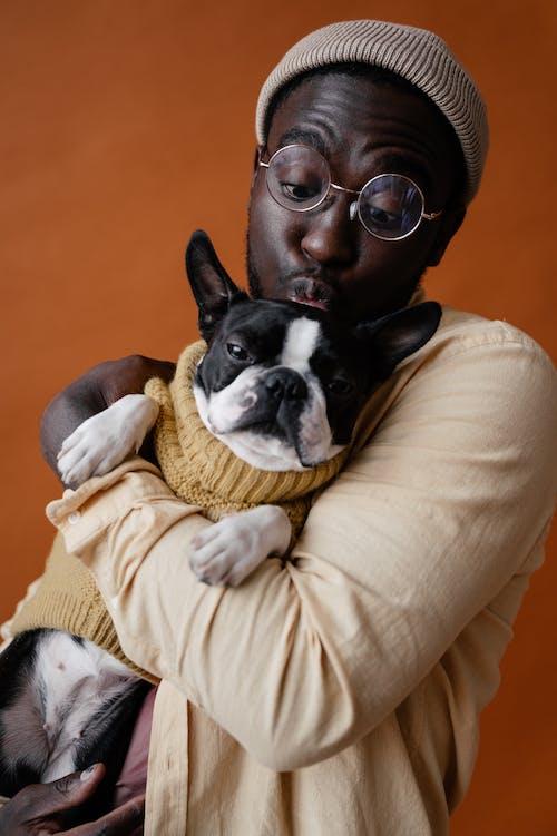 Cute black man kissing dog on head