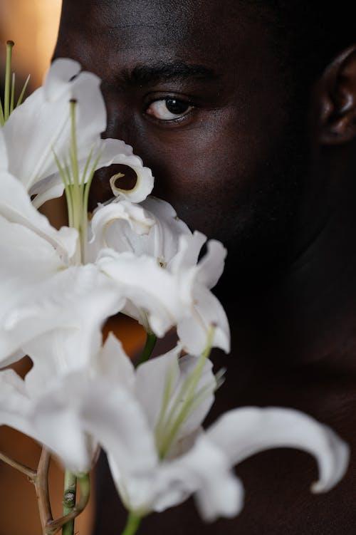 Black man holding white flowers