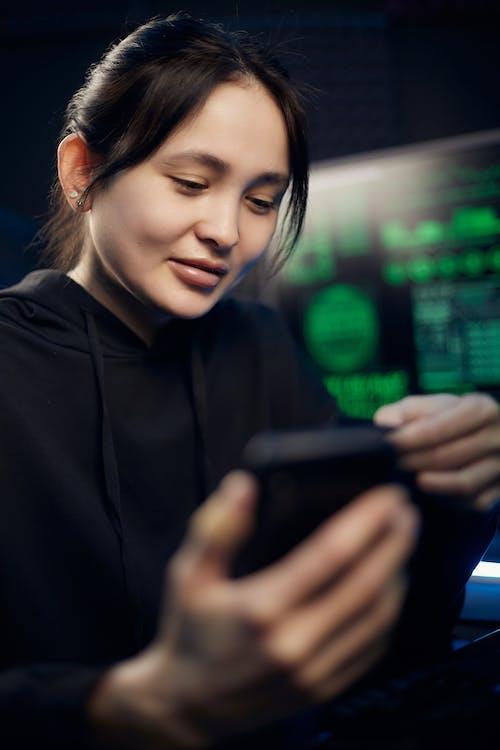 Woman in Black Long Sleeve Shirt Holding Black Smartphone