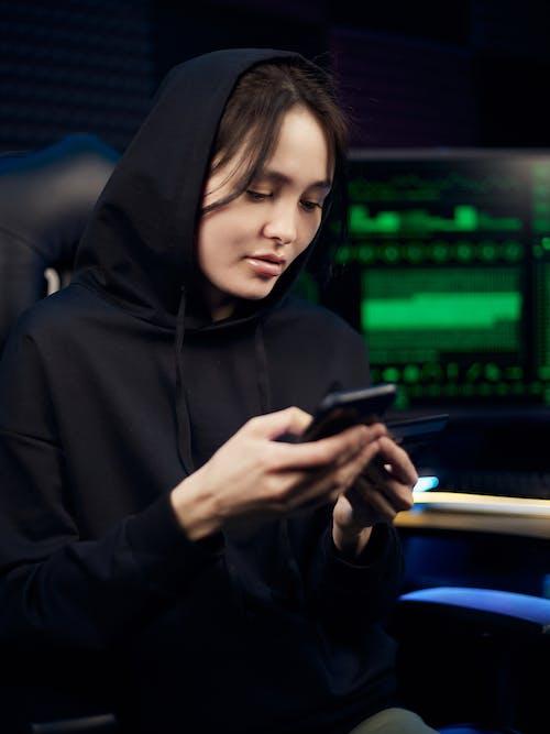 Woman in Black Hoodie Holding Smartphone