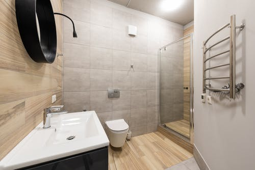 Contemporary interior of bathroom with shower and toilet designed in minimal style in new apartment