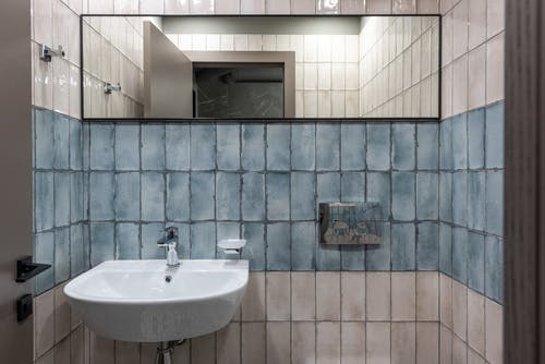 Interior of modern restroom with ceramic white sink and mirror hanging on white and blue tiled wall