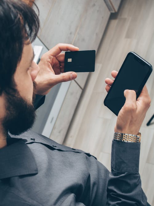 Man in Gray Sweater Holding Black Smartphone