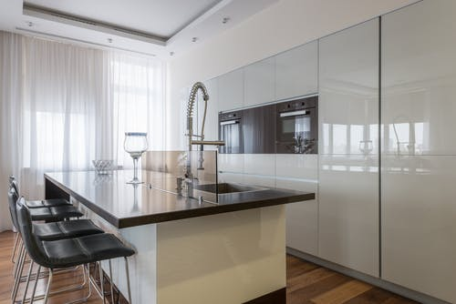 Minimalist interior of spacious kitchen with built in ovens and island