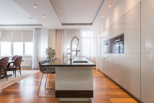 Interior of spacious kitchen with modern minimalist furniture with built in appliances and dining zone in contemporary apartment in daylight
