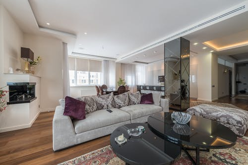 Small glass black table placed on carpet near sofa with pillows in spacious light living room in apartment in daytime