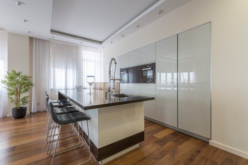 Interior of contemporary spacious kitchen zone stylish expensive furniture in luxury apartment in daytime