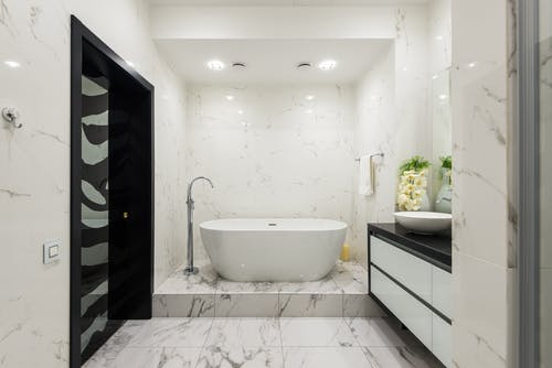 Interior of contemporary bathroom with light tiled walls and white ceramic bathtub in luxury apartment in daytime