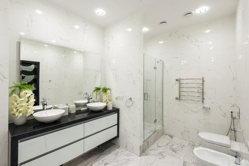 Interior of contemporary light bathroom with marble walls and floor and white furniture in luxury apartment