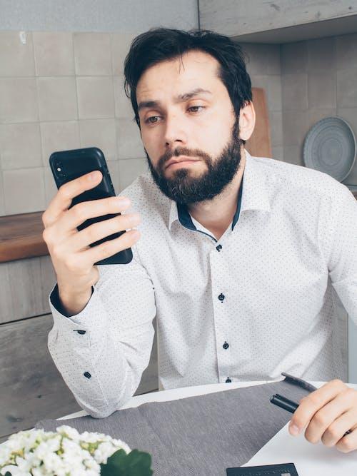 Man in White and Black Polka Dot Dress Shirt Holding Black Smartphone