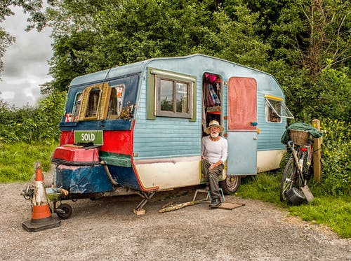 Photo Of A Man In White Long-sleeved Top on Blue And White Pop-up Camper