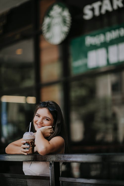 Young woman holding coffee near cafe