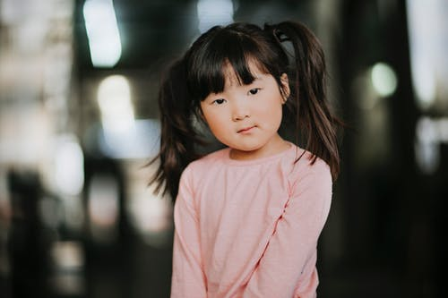 Adorable little Asian girl with ponytails wearing pink shirt looking at camera on blurred background