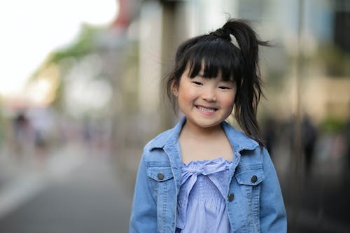 Asian girl smiling and standing on street