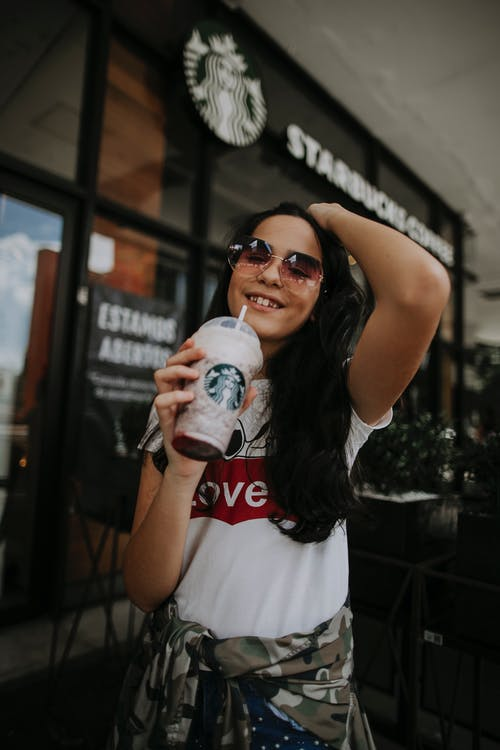 Cheerful ethnic female teenager in casual clothes and sunglasses smiling and touching long dark hair while drinking cold takeaway coffee with straw near modern cafe in city
