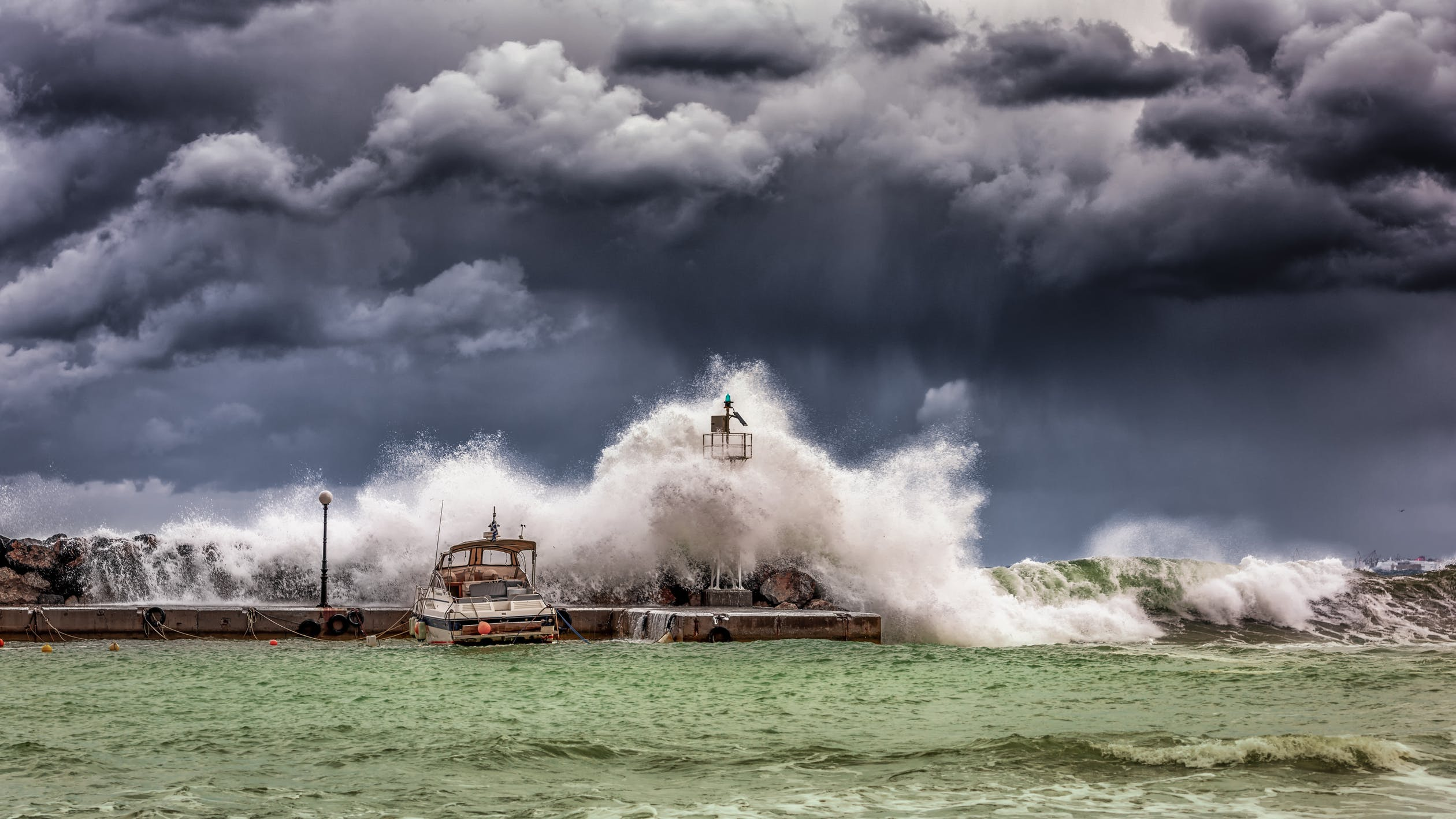Storm over water with big waves crashing into boat and dock