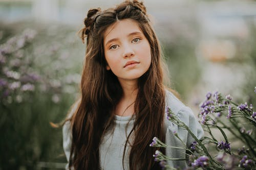 Charming girl with long hair in blooming meadow