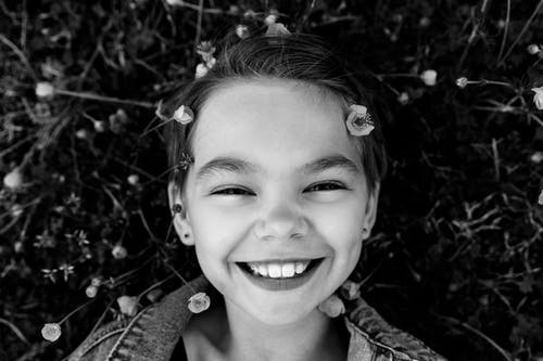 Grayscale Photo of Girl Smiling