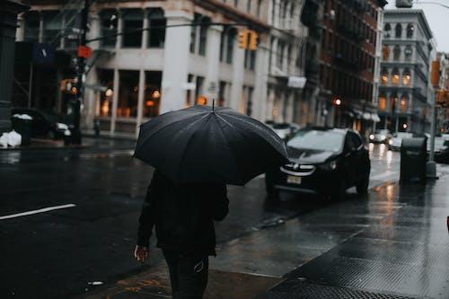 Person in Black Jacket Holding Umbrella Walking on Sidewalk