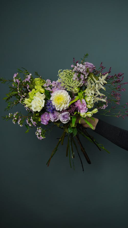 Crop person showing blooming floral bouquet on gray background