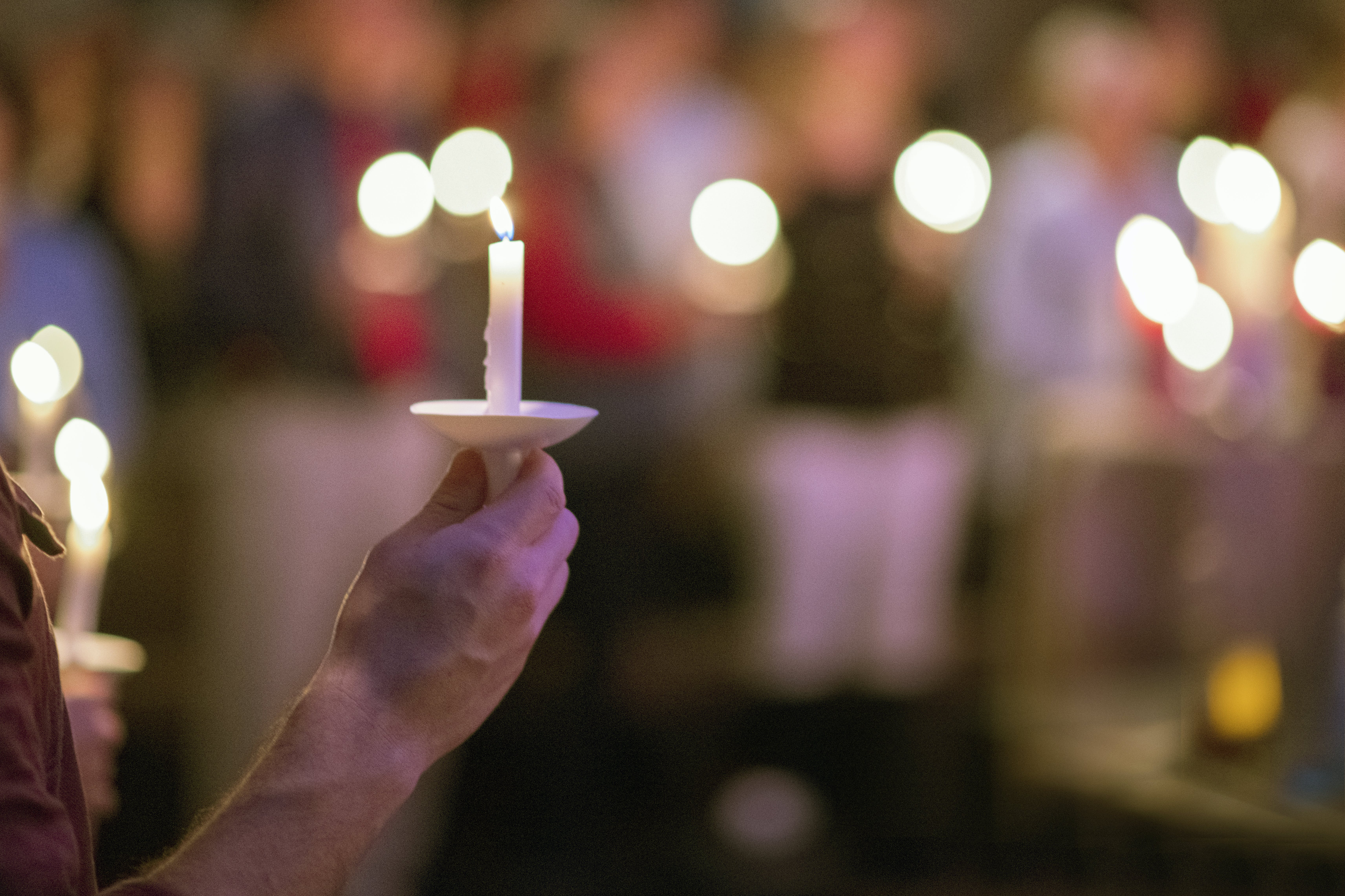 Person Holding White Taper Candle