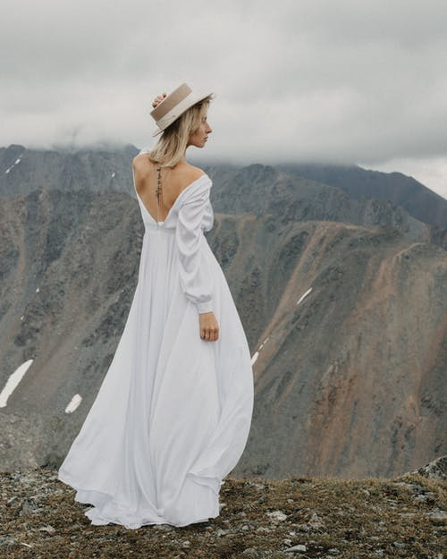 Back view of tender female in bridal dress and hat admiring majestic mountain with snow on wedding day