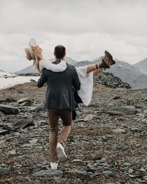 Anonymous trendy man carrying happy female beloved in white dress and boots while walking on mount with snow on wedding day