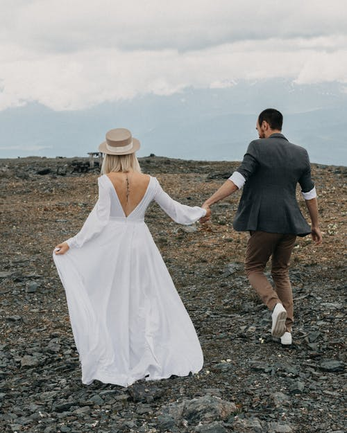 Anonymous groom and bride walking on rocky land