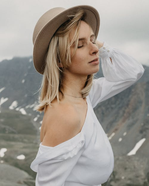 Side view of mindful woman with closed eyes in white apparel against mountain on wedding day