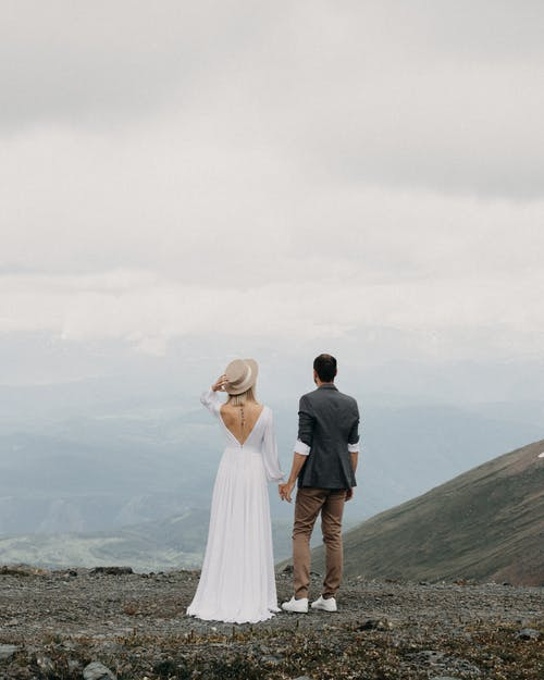 Back view of anonymous groom and bride holding hands while contemplating ridges under cloudy sky in foggy weather