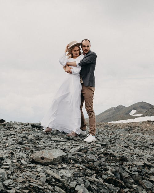 Newlywed couple embracing against ridge under cloudy sky