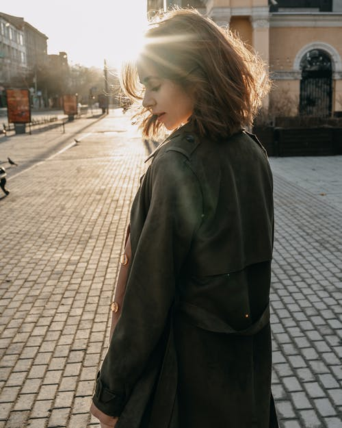 Young woman standing on sidewalk on street in sunlight