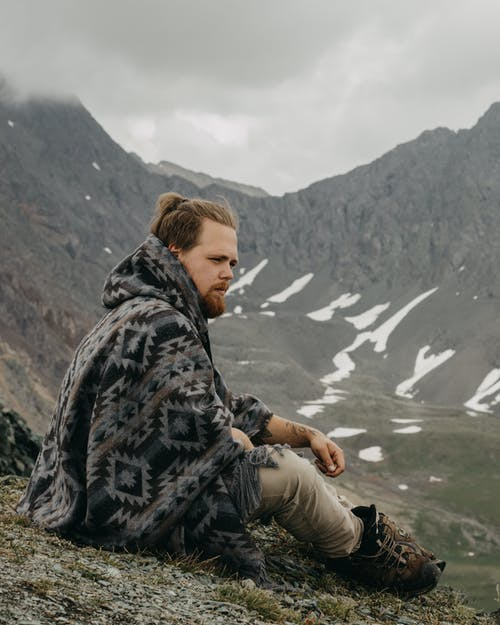 Side view of male traveler in poncho sitting on hilltop while contemplating majestic mountain in foggy day