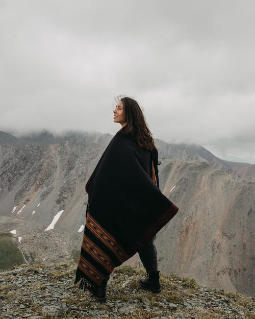 Ethnic female in warm cloak standing on edge of precipice in mountains and looking away in cloudy day