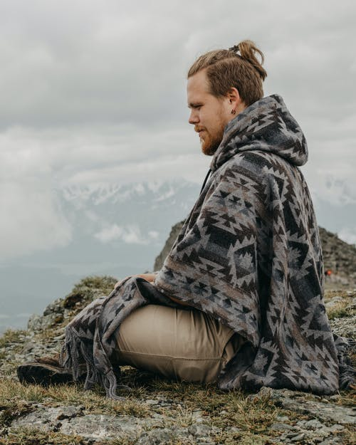 Side view of male tourist in poncho sitting on top of mountain against cloudy sky