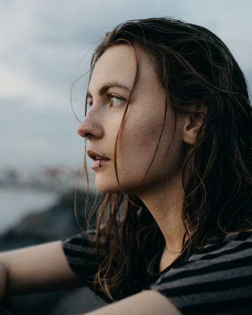 Side view of young dreamy female with lip piercing and wet hair looking away thoughtfully while sitting on shoreline