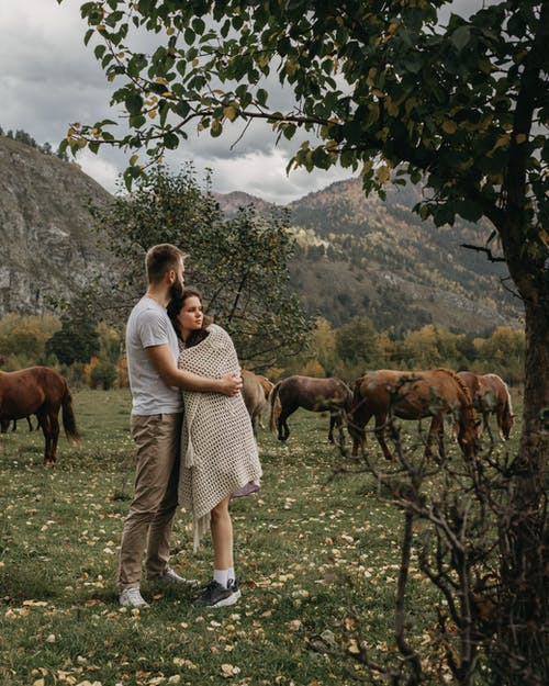 Couple hugging against mountains and horses
