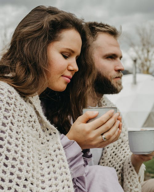 Side view of couple in knitted shawl drinking hot beverage against blurred background in nature