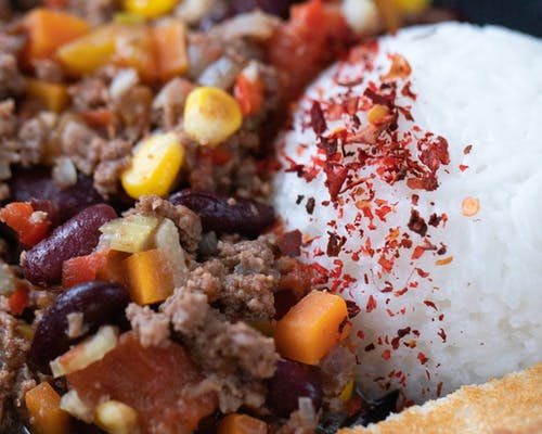 Closeup of tasty main course with ball of rice near chopped vegetables mixed with ground meat
