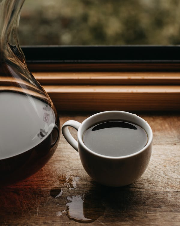 Mug with coffee near glass vessel on windowsill