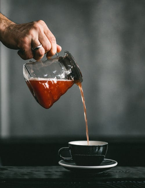 Crop person pouring coffee into cup on gray background
