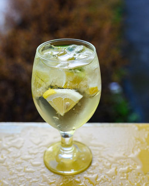 Glass of cold cocktail with lime mint and sliced lemon placed on wet table