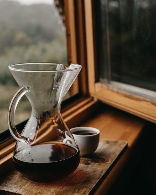 Chemex with coffee and cup near window