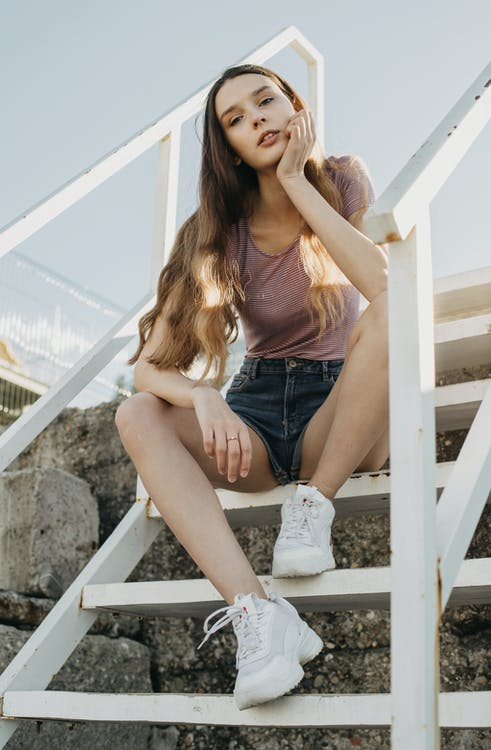 Full body of young female in casual clothes sitting on wooden steps and looking at camera