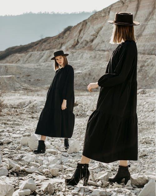 Full body of young alike women in similar black dresses and hats standing opposite each other on stony ground in desert