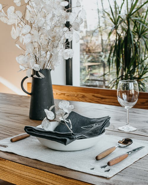 Artificial bouquet and dishware placed on table