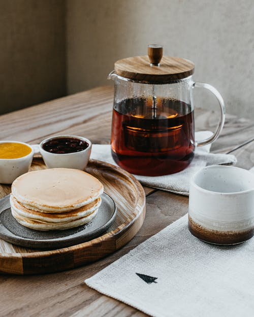 From above cup and kettle of tea served on table near pancakes on plate and honey and jam in cups